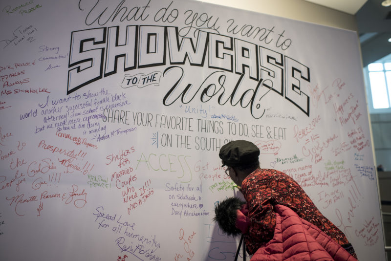 A woman writes on a South Side Showcase installation at an Obama Foundation public meeting.