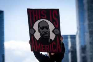 """A protestor holds up a sign of George Floyd's face surrounded by the words """"This is America."""""""