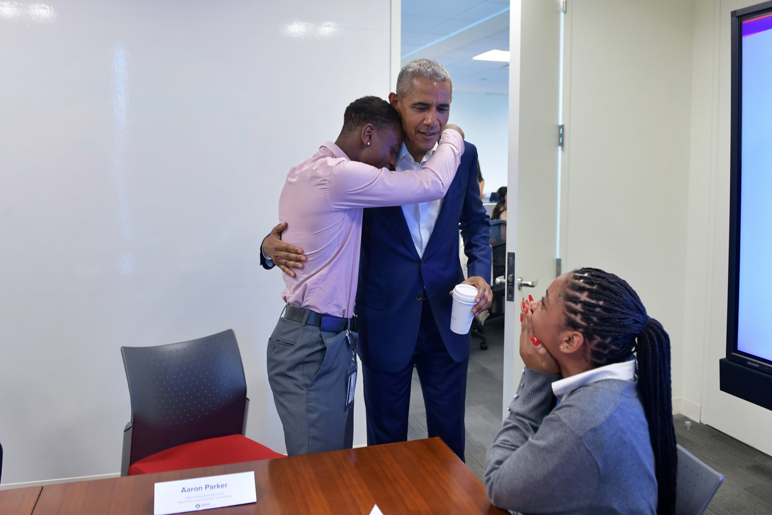 A young man hugs President Obama from the side as he holds a cup of coffee.