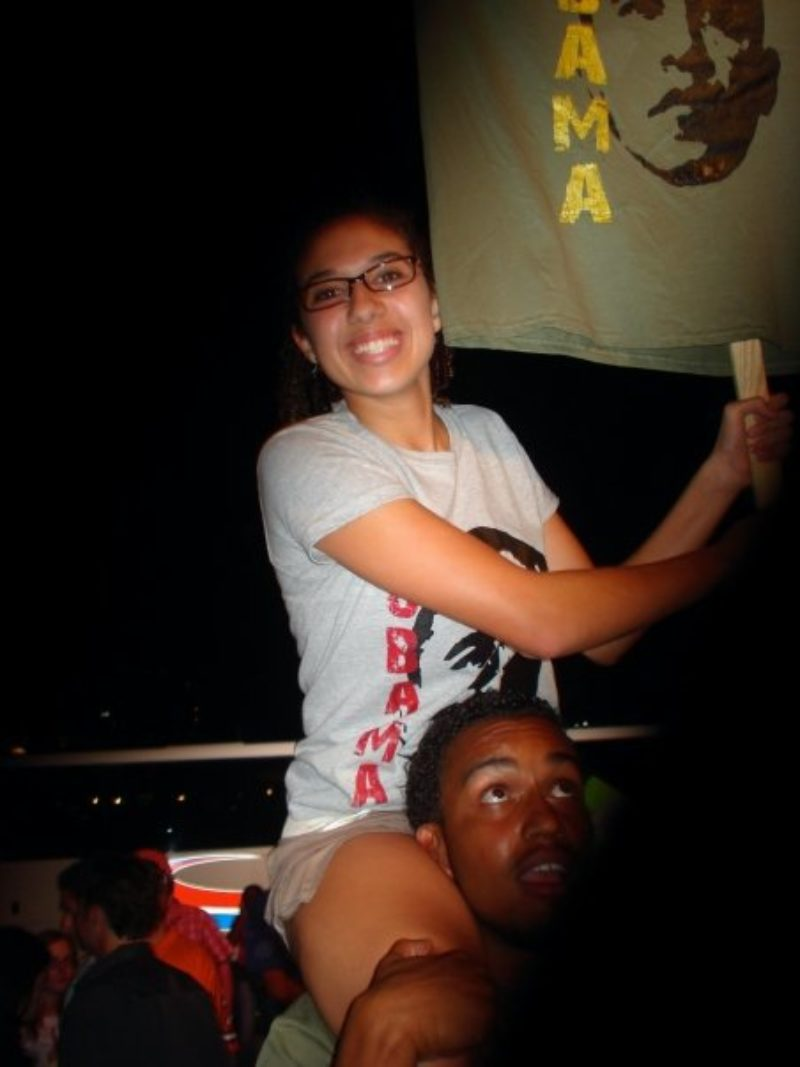Woman sits on a young man's shoulders holding a pro-Obama sign.