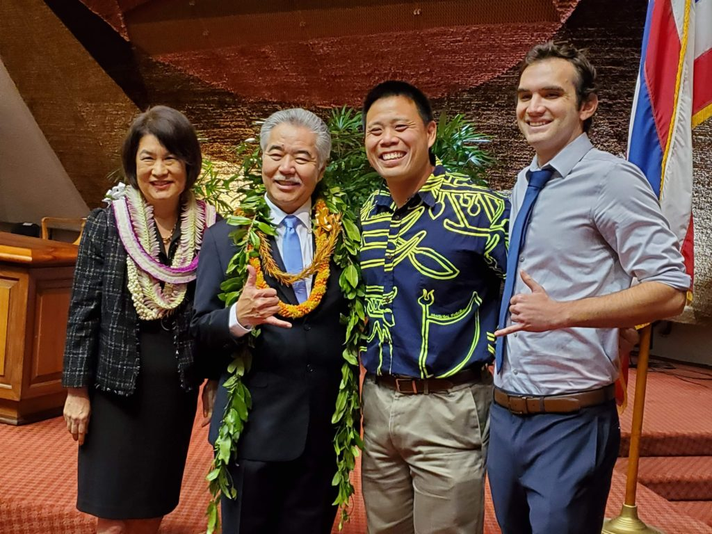 Fellow John Leong smiles to camera with Hawaii Governor Ige and two additional staff.