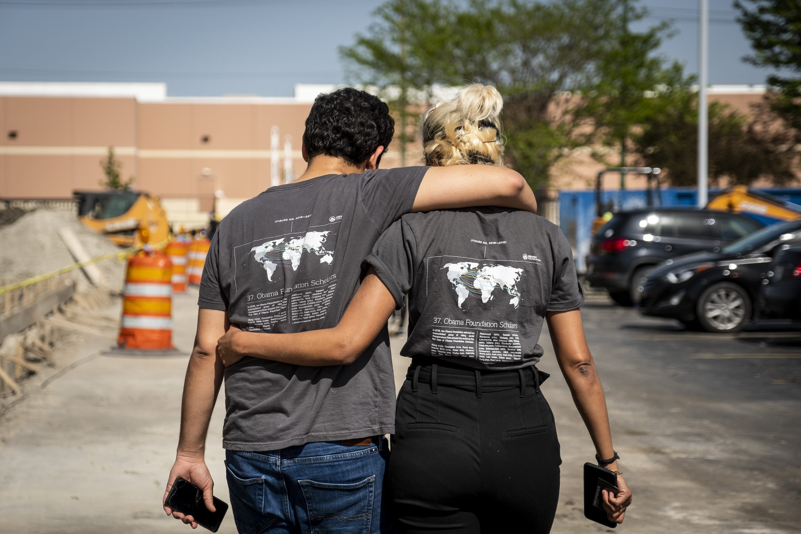 A young woman and man are photographed from behind with their arms around each other in a display of friendship.