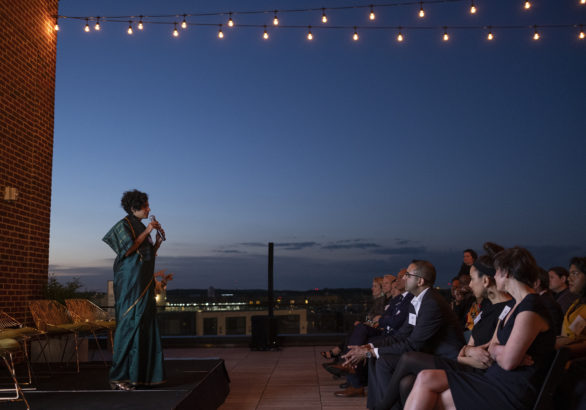 Obama Fellow Preethi Herman speaks to a group of people against a beautiful sunset.