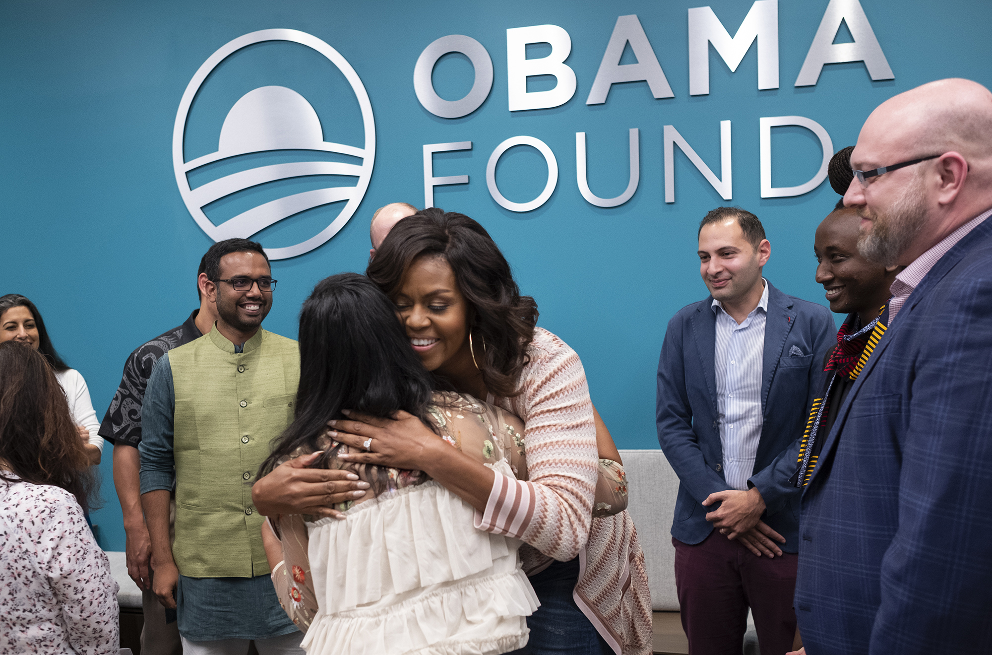 Mrs. Obama hugs a young woman as a group of people look on.