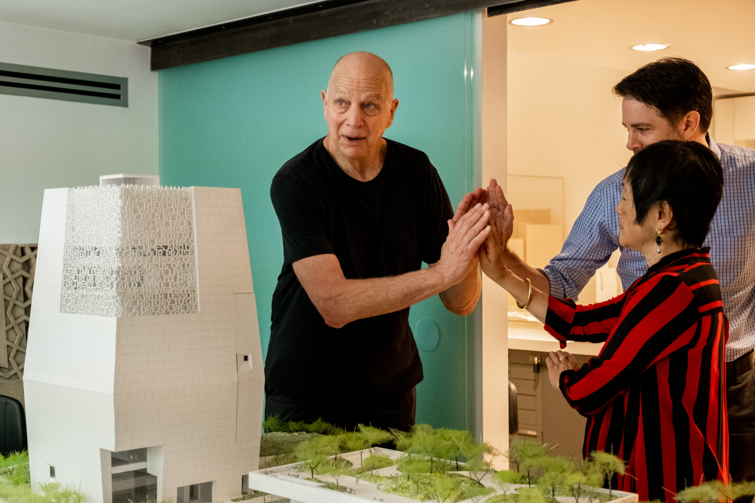 Tod Williams and Billie Tsien place their hands in the same shape as the model of the Obama Presidential Center.