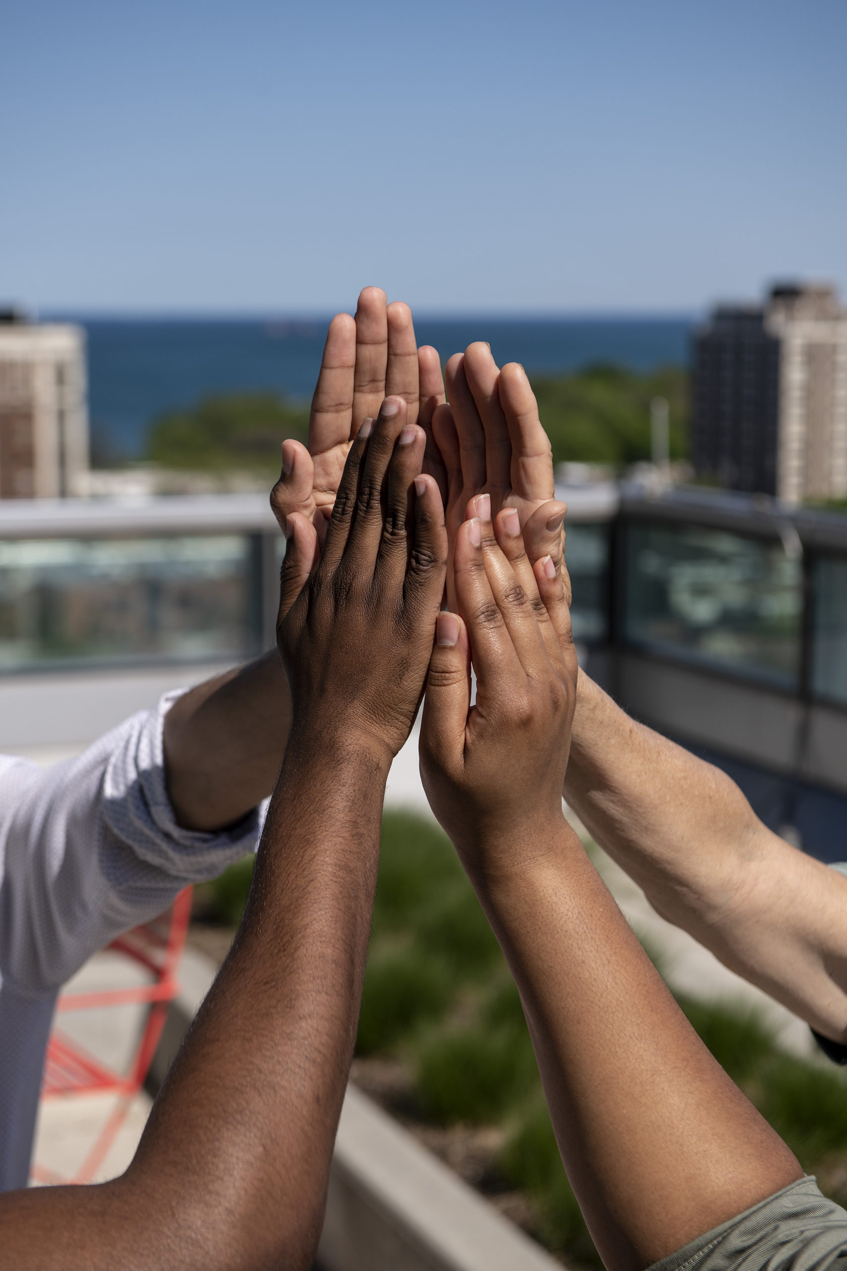Four hands demonstrate the shape of the Obama Presidential Center tower against the Chicago skyline.