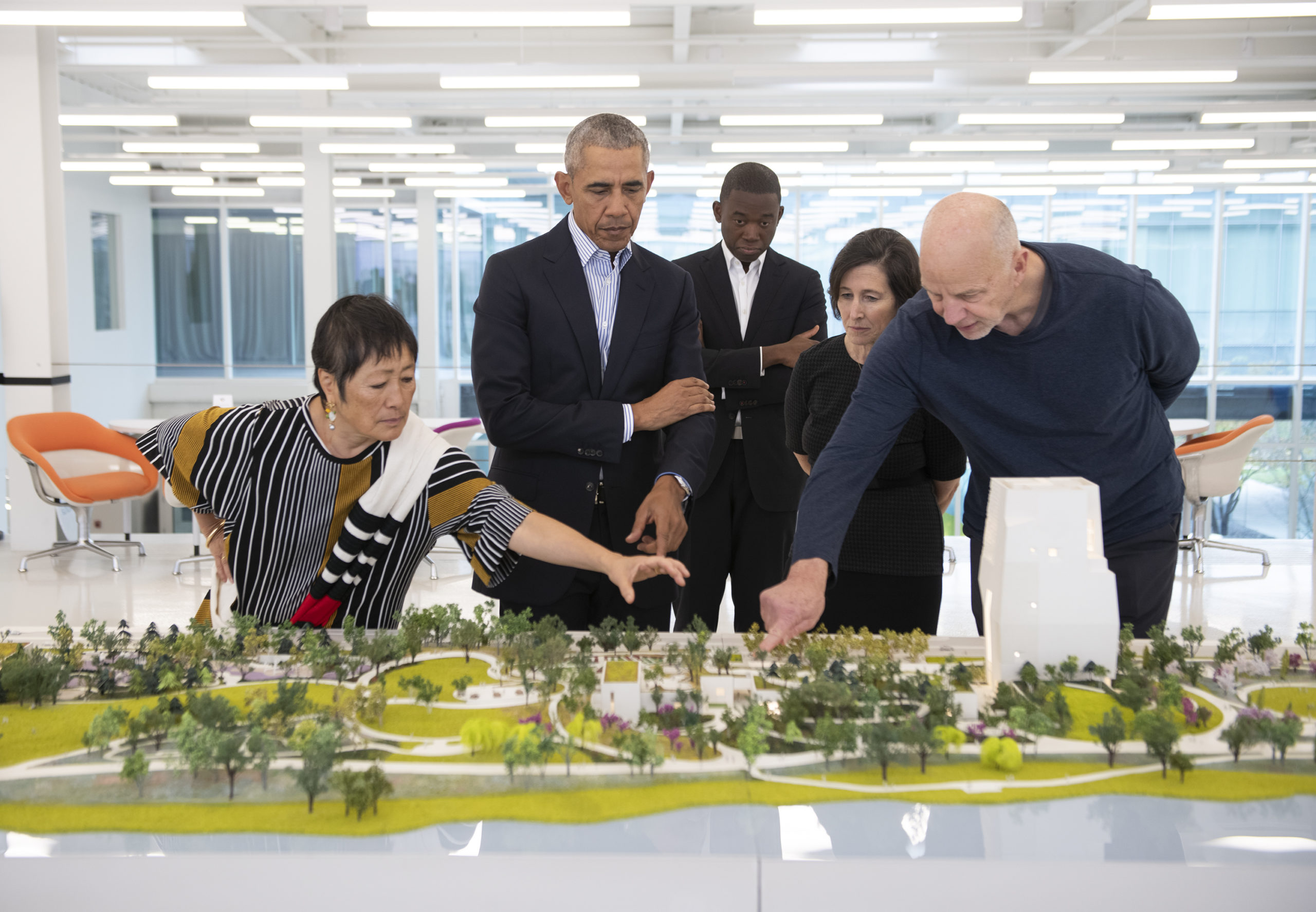 Tod Williams and Billie Tsien point to features of the Obama Presidential Center as President Obama looks on with his arms crossed.
