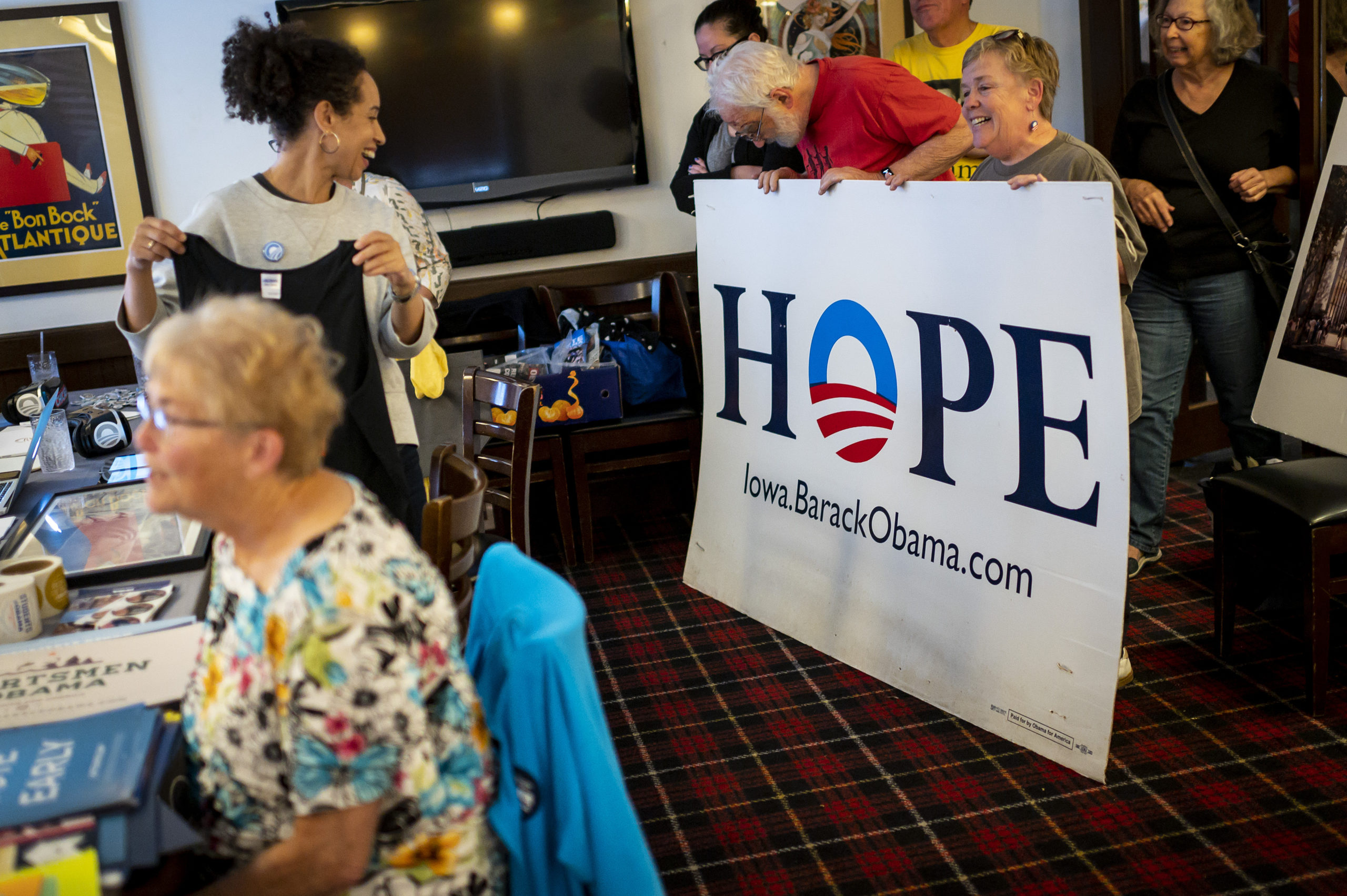 Louise Bernard reacts as supporters of President Obama's campaigns hold up a poster that reads