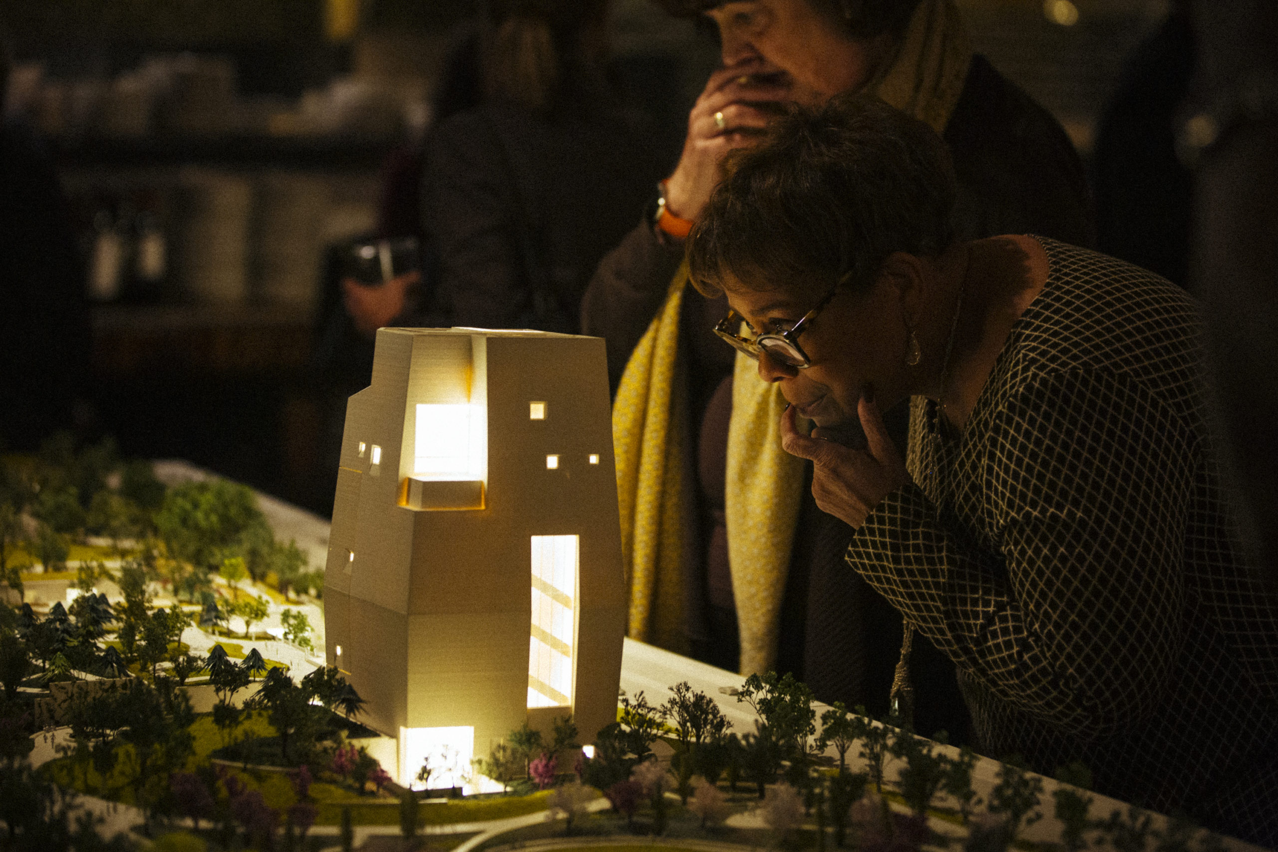 Two women peer into the lit windows of the Obama Presidential Center model.