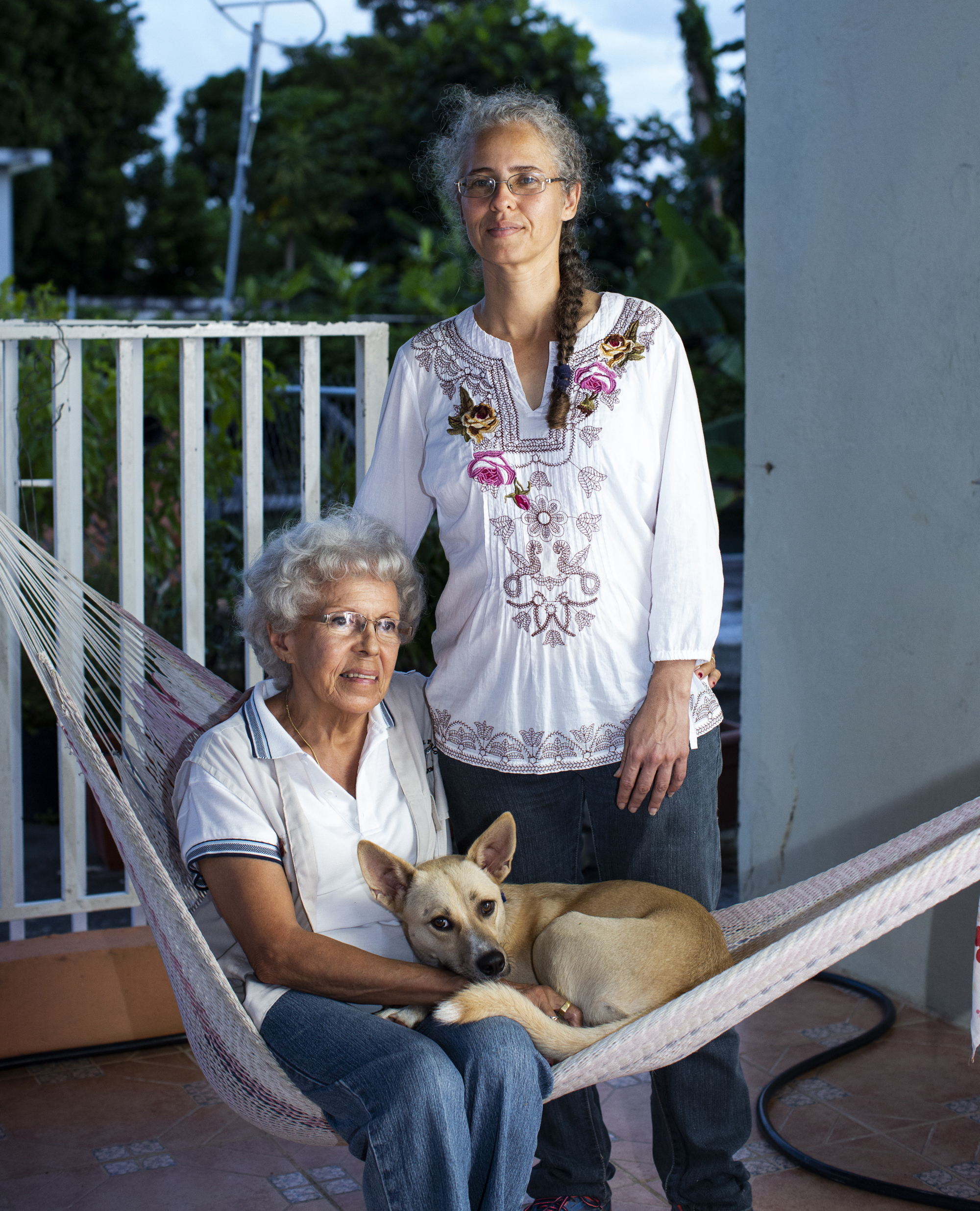 Alana Feldman Soler stands on the porch as her mother and dog rest on a hammock.