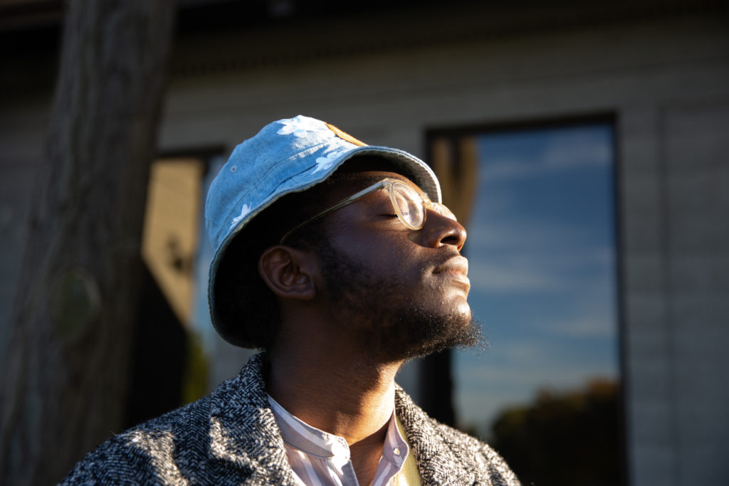 Community Leadership Corps participant Oluwaseyi Adeleke takes in the warming sun with his eyes closed.