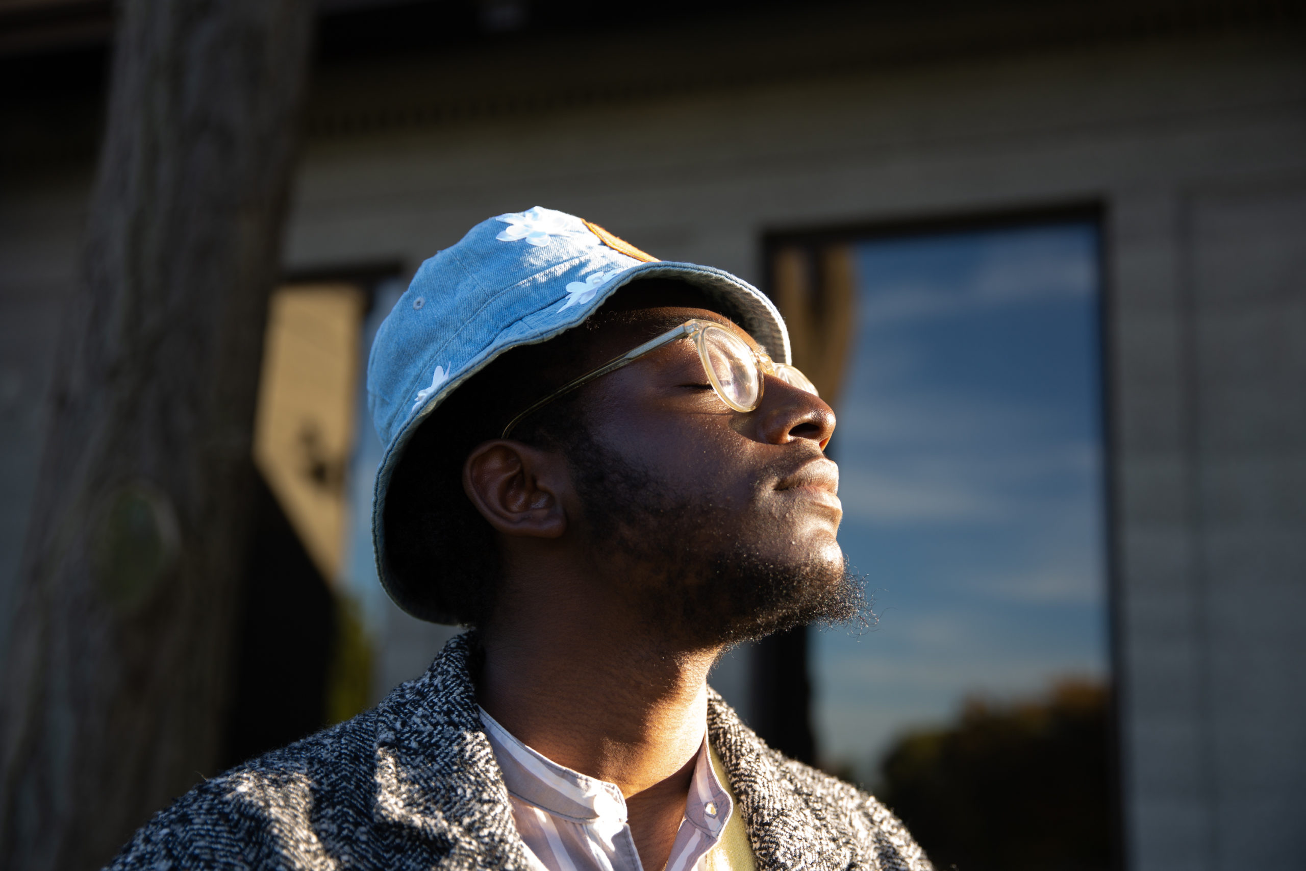 Community Leadership Corps member Oluwaseyi Adeleke takes in the warming sun with his eyes closed.