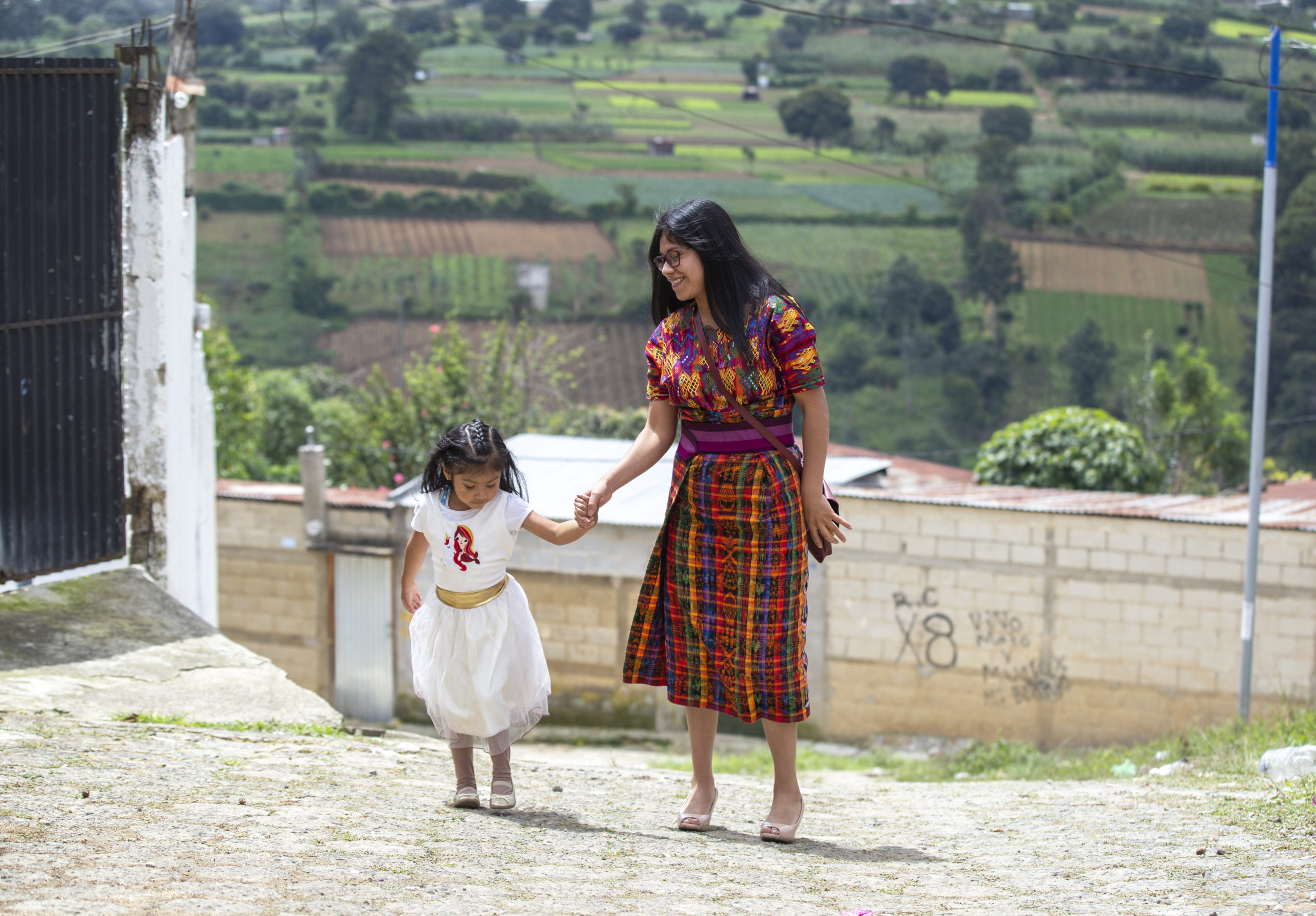 Ancela Ortiz holds her young daughters hand with pastures in the background.