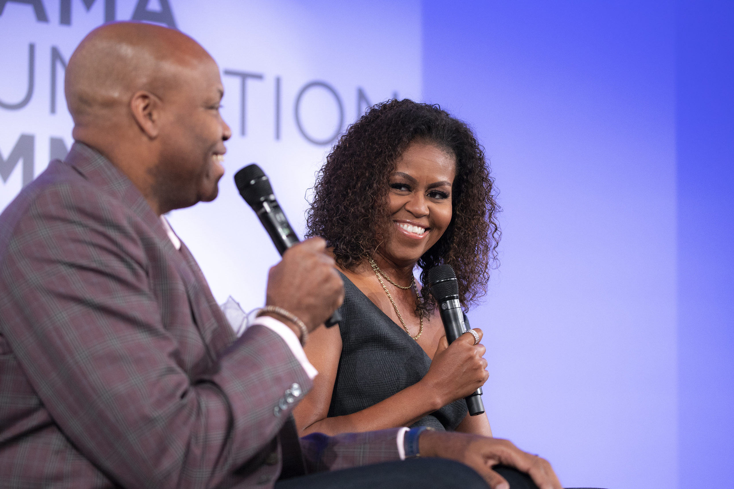 Mrs. Obama gives a knowing smile to her older brother, Craig, as he speaks into a mic.