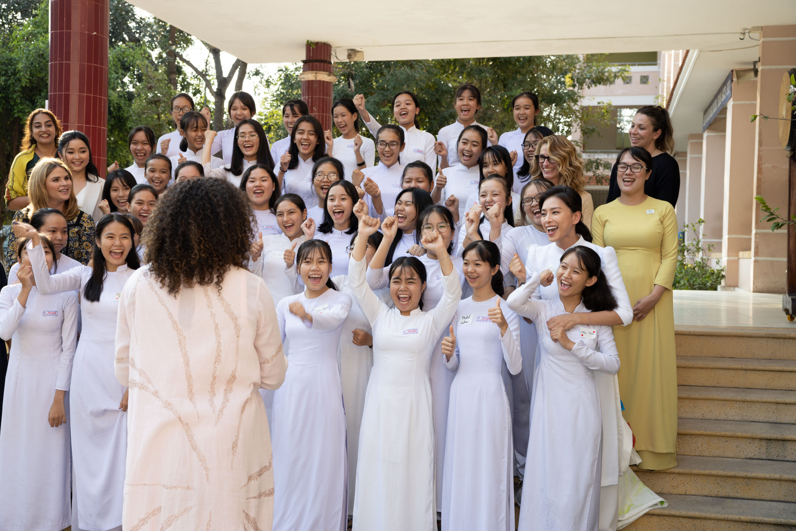 Mrs. Obama faces a group of excited young girls wearing white robes with their hands above their heads in joy.