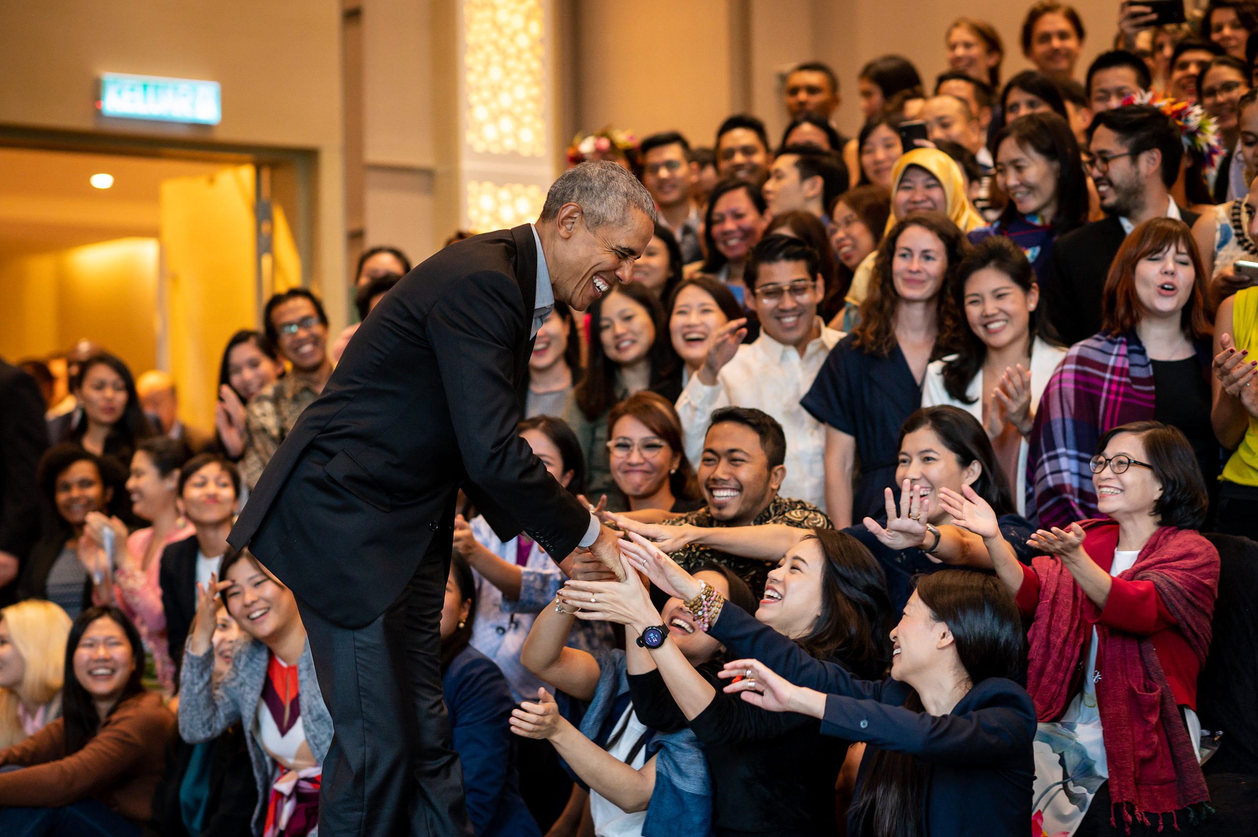 President Obama smiles as he shakes hands with an excited crowd of young people extend their hands.