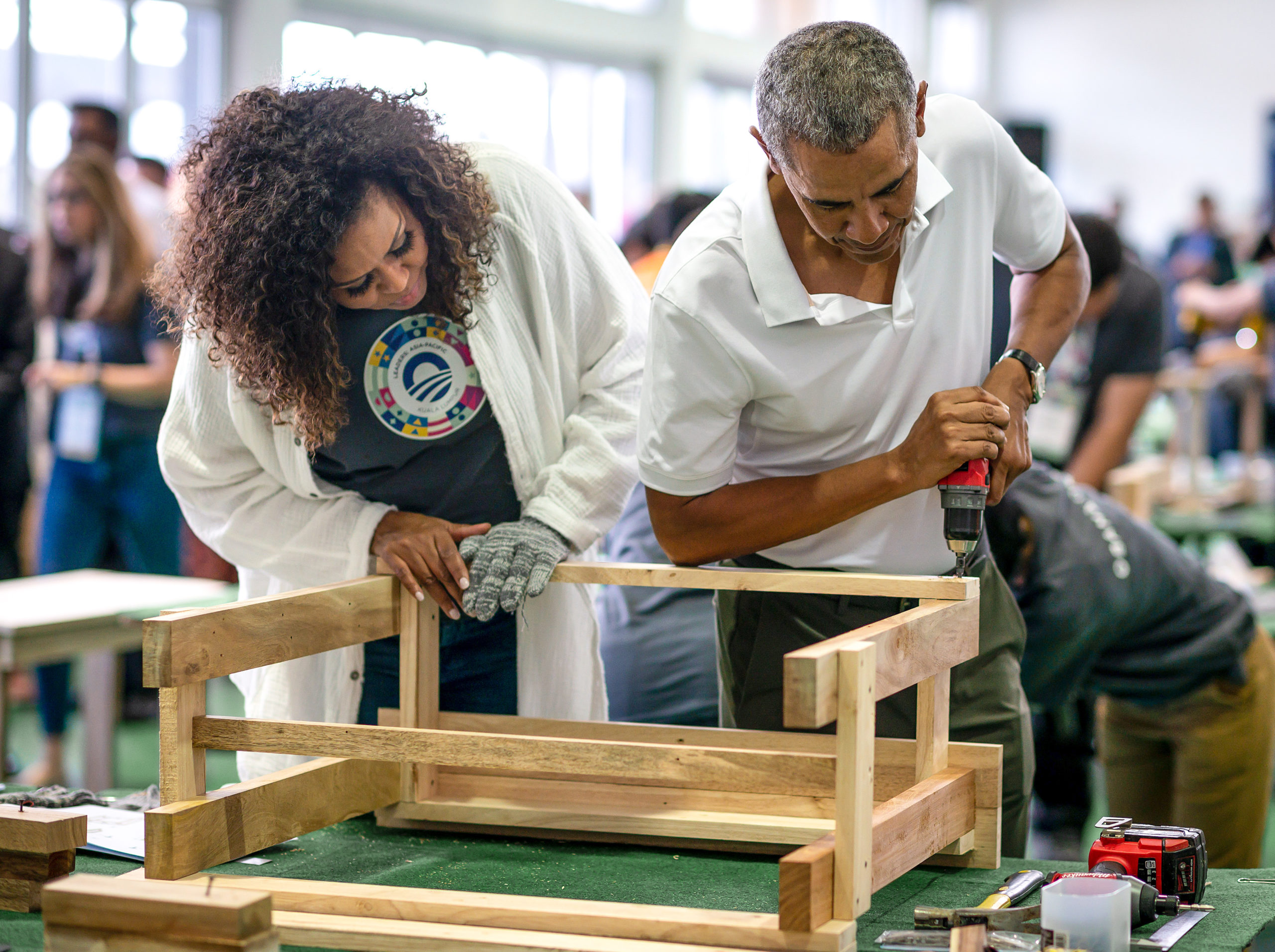 President Obama drills into a piece of furniture as Mrs. Obama looks on.