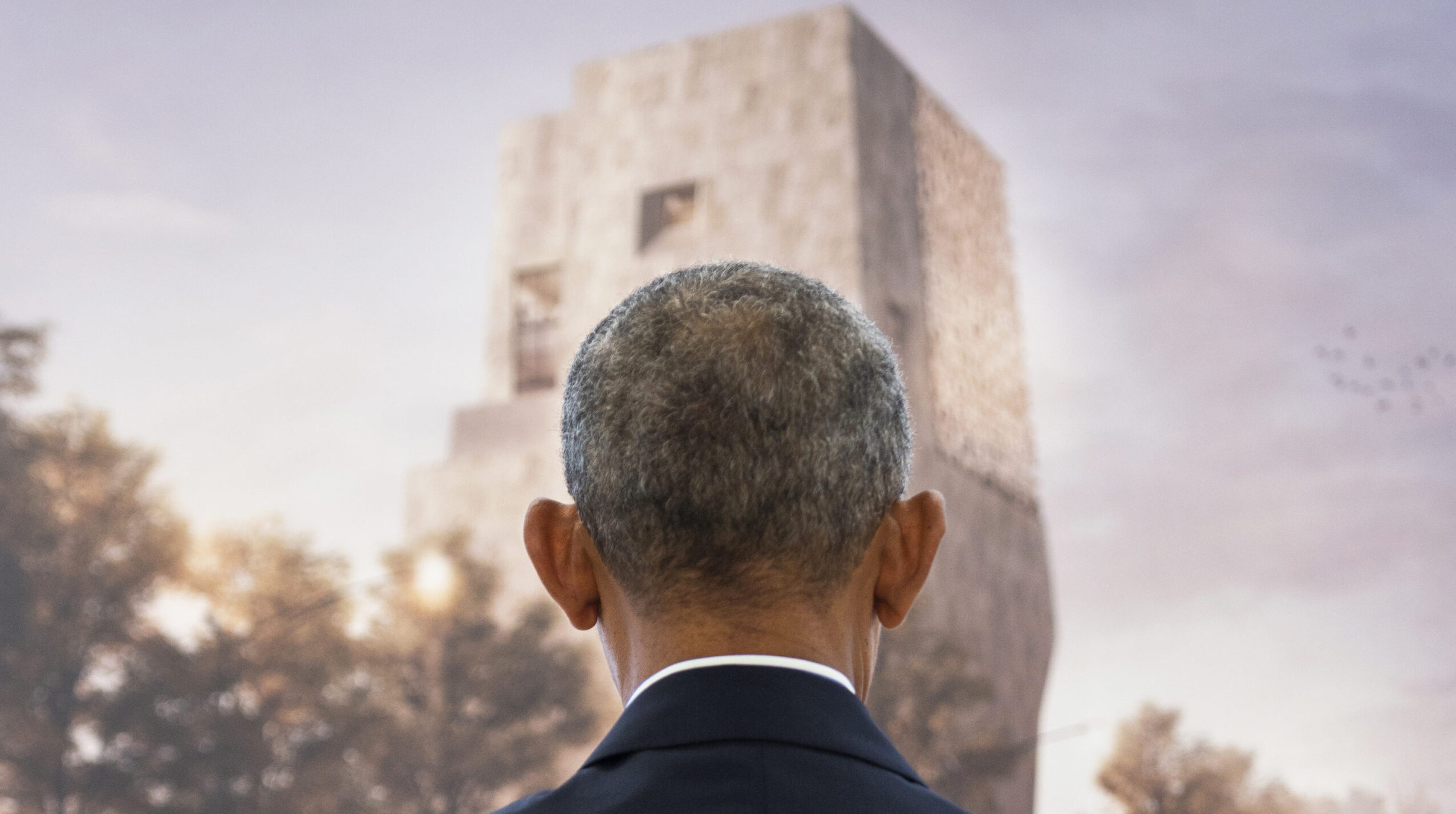 President Obama is photographed from behind looking at a rendering of the Obama Presidential Center.