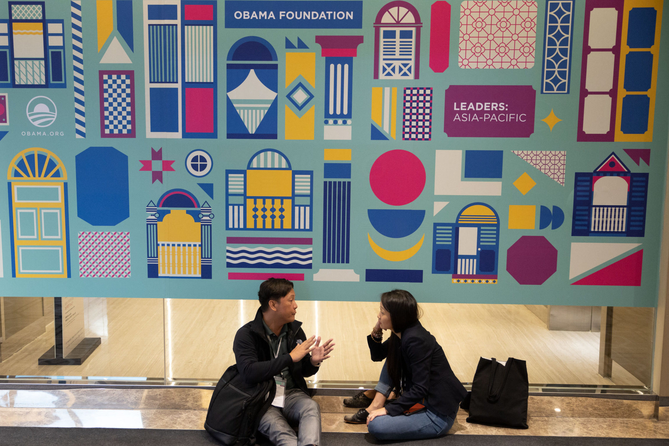 Two young Leaders sit under a banner designed by Valen Lim Chong Chin.
