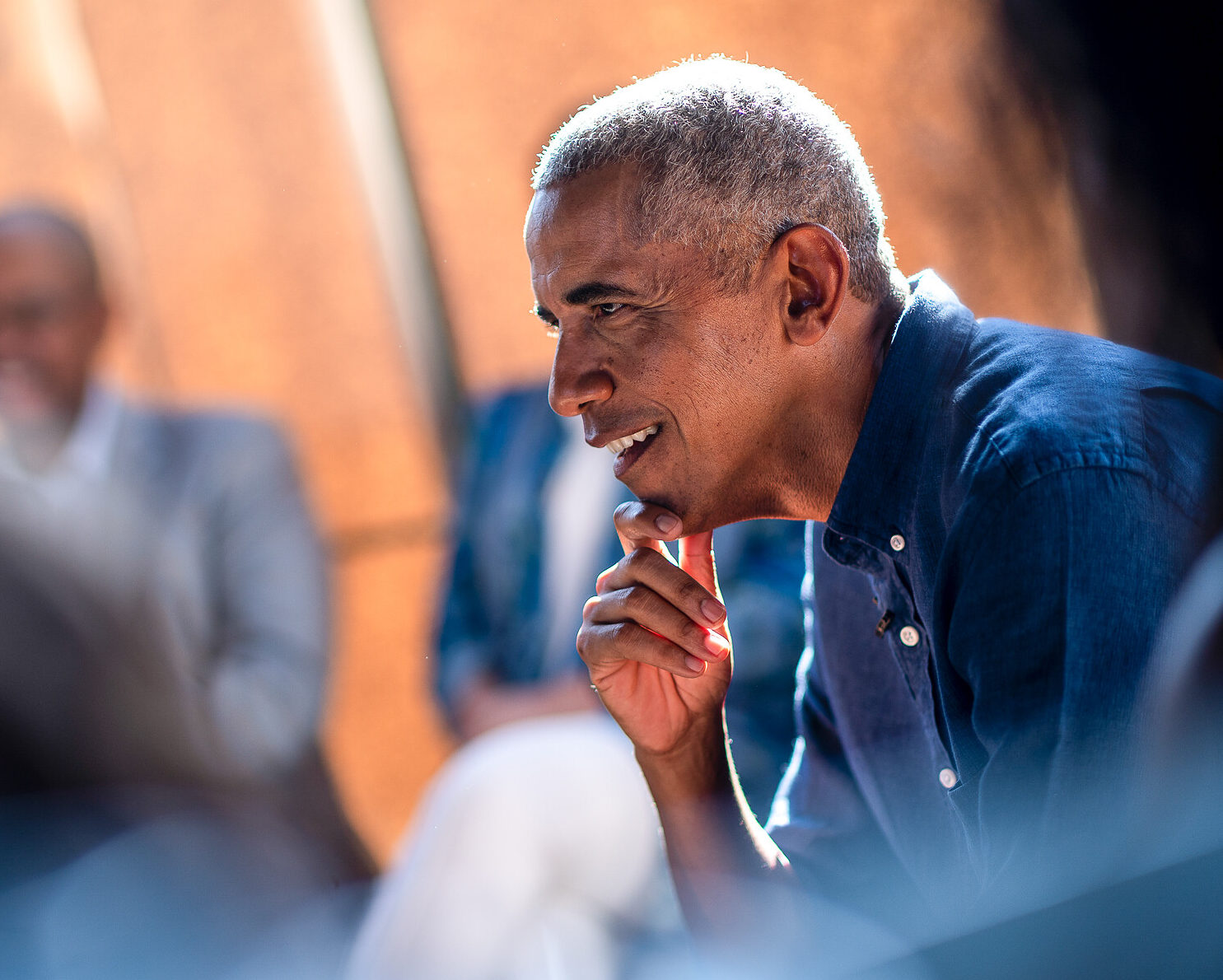 A side profile of President Obama smiling with his hand resting on his chin.