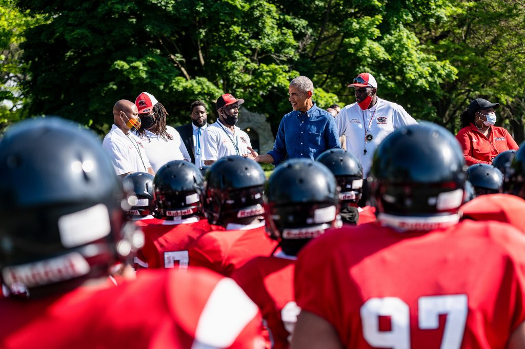 President Obama is seen amongst the backs of football helmet-wearing young people