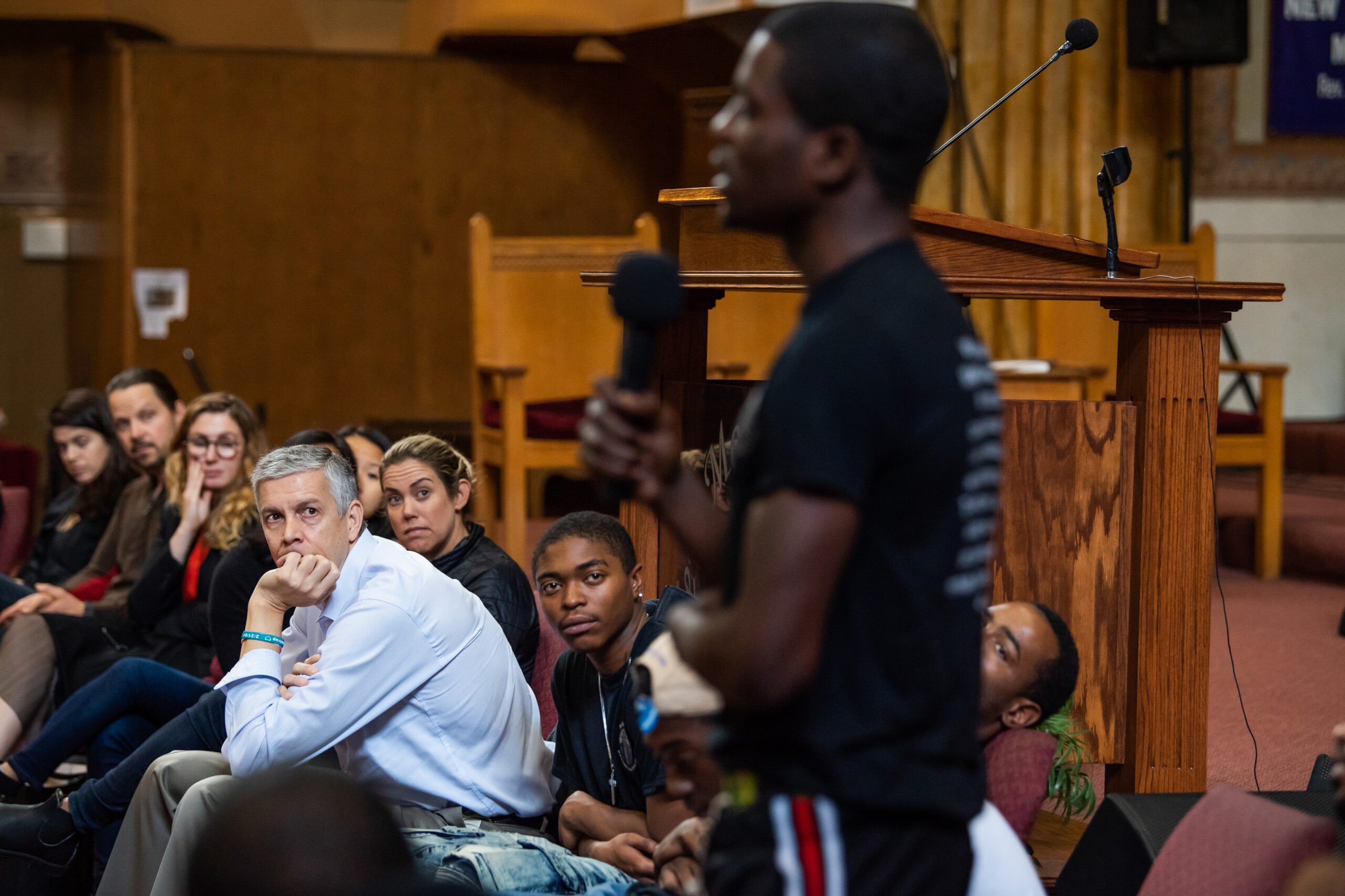 Arne Duncan watches a young man speaking to a crowd with a microphone.