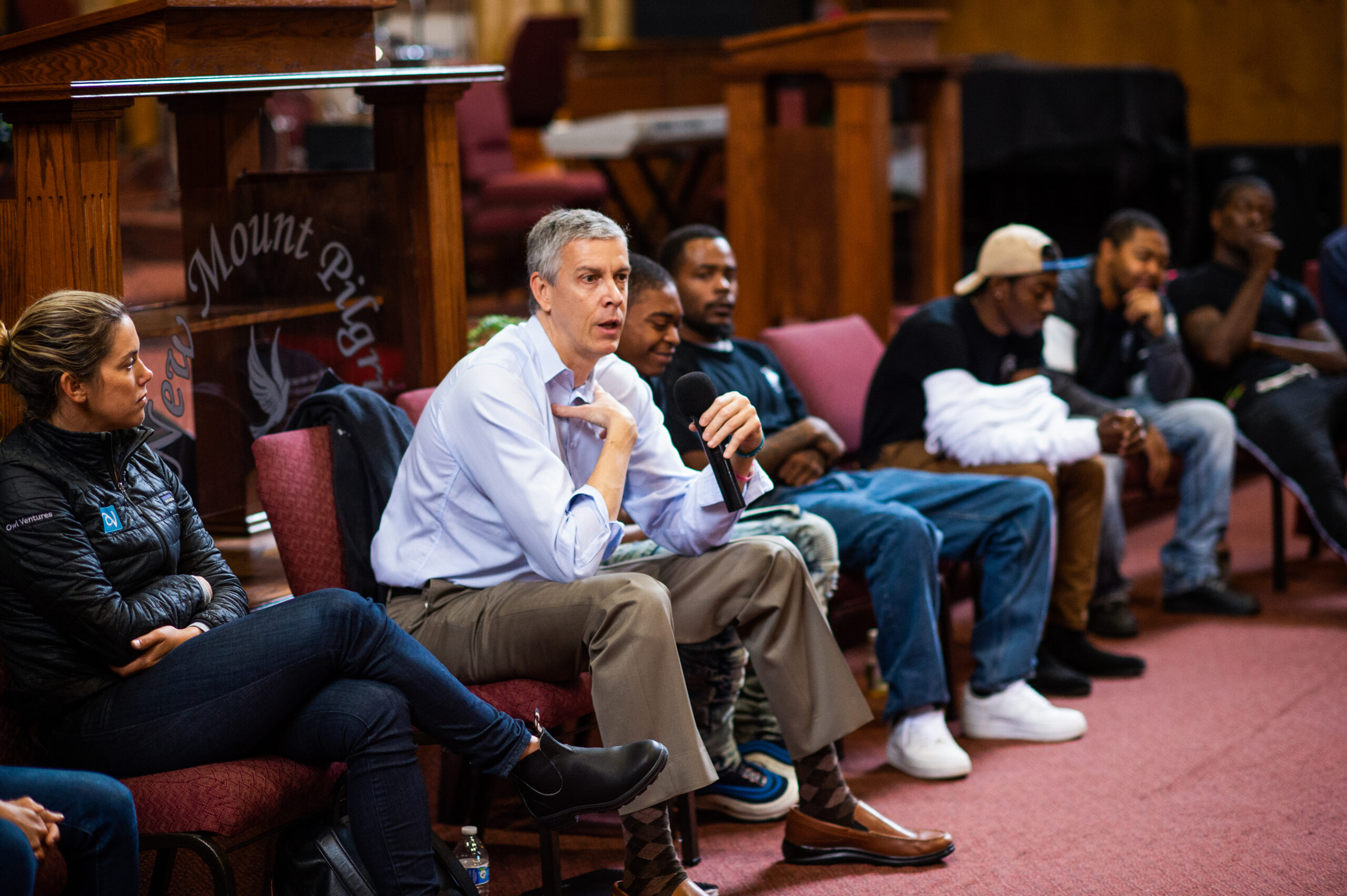 Arne Duncan, former Secretary of Education, holding a microphone addresses a crowd of young men of color.