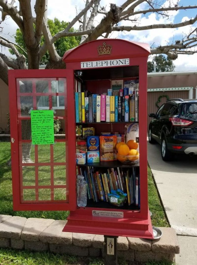 A red telephone booth is filled with books for people to take for free.