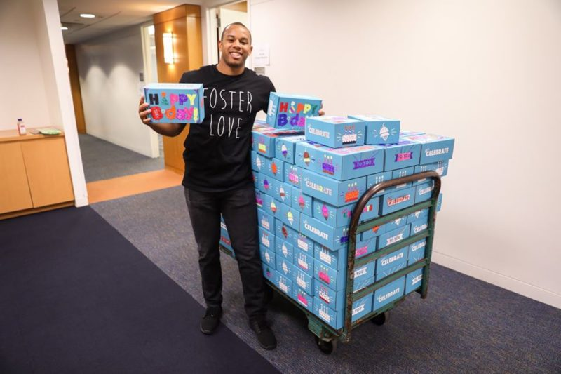 A man smiles next to a large cart holding dozens of birthday boxes for children in need.