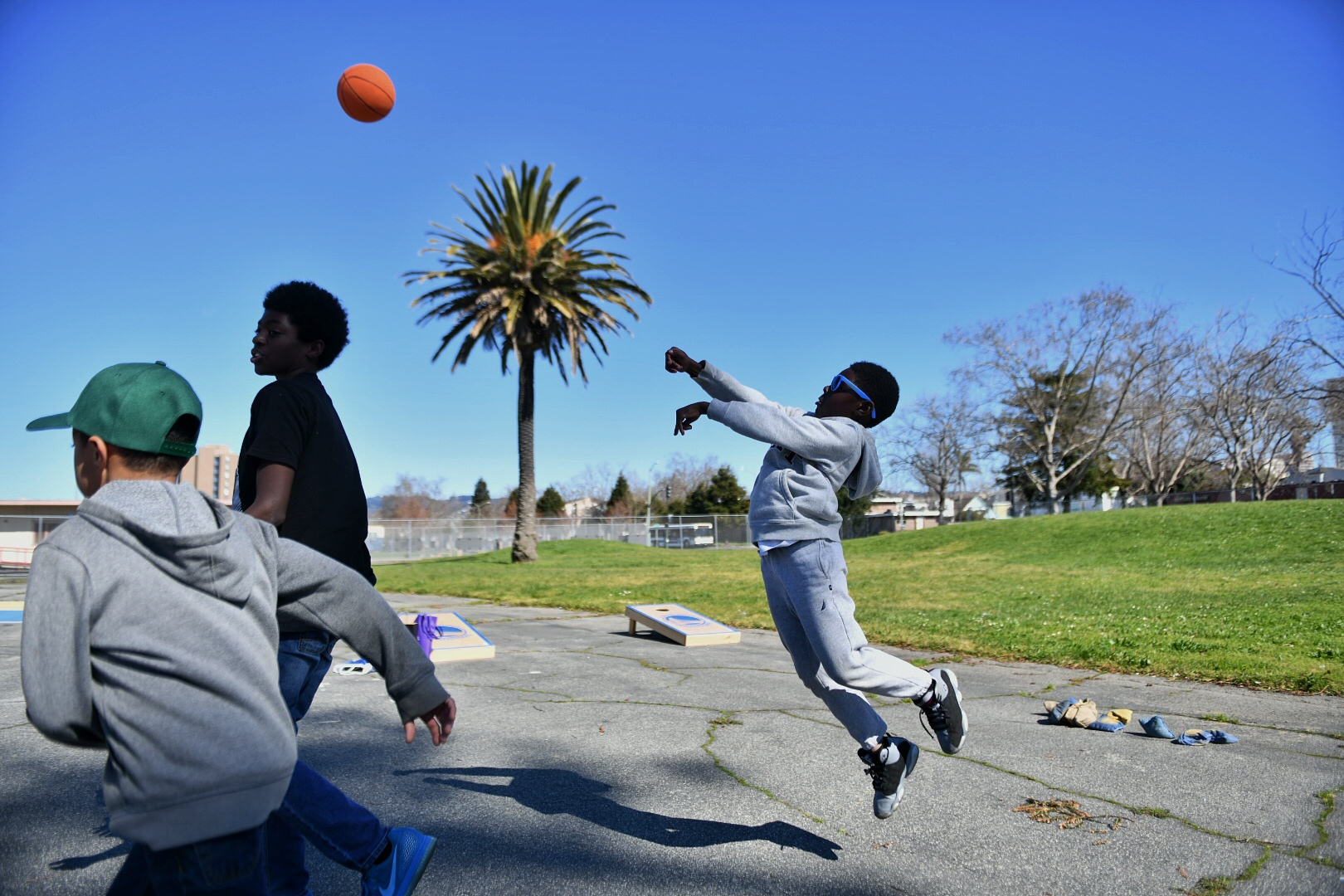 Young men playing basketball during MBK Rising Day of Service