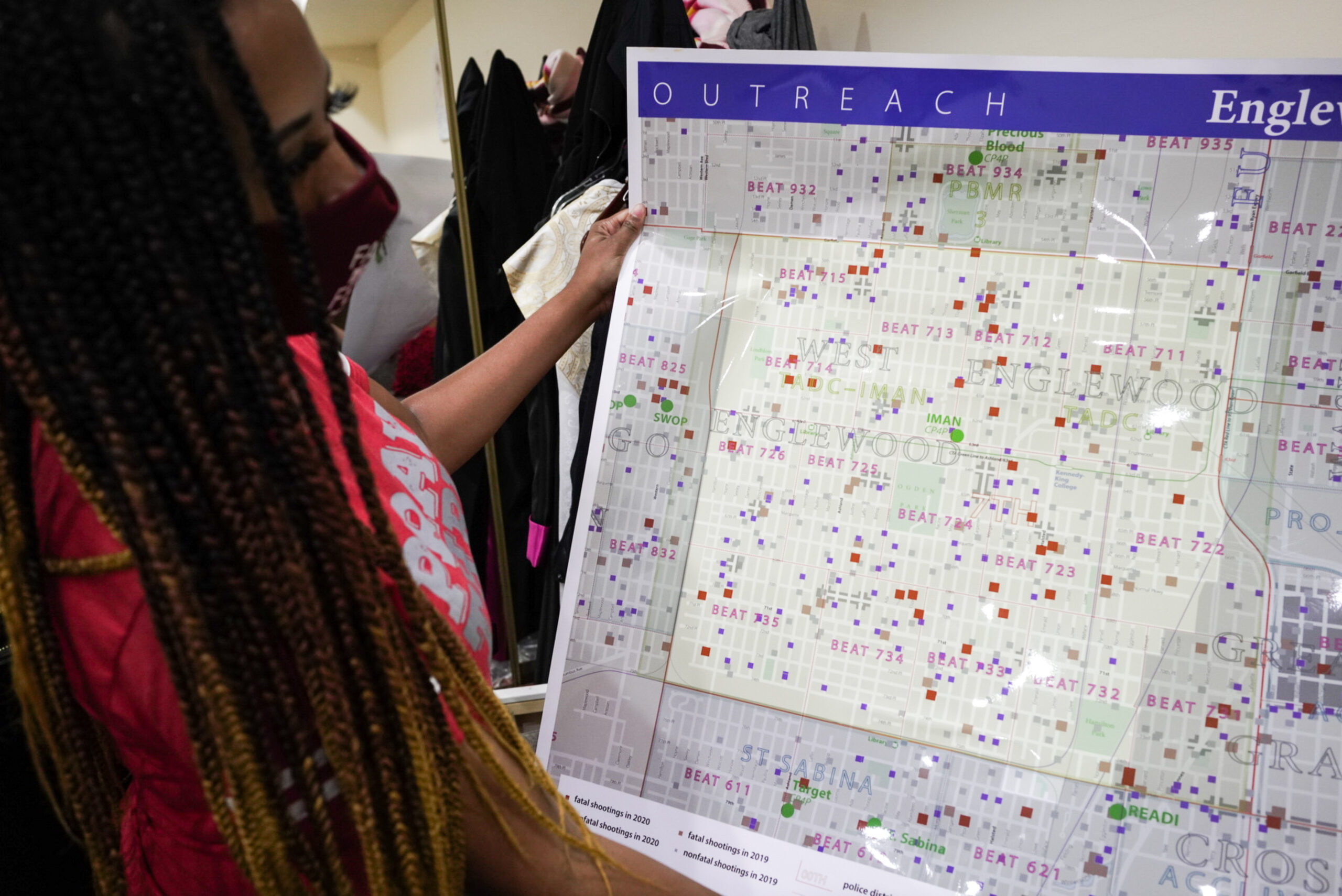 A woman holds up a map of the Englewood neighborhood of Chicago indicating where shootings have occurred.