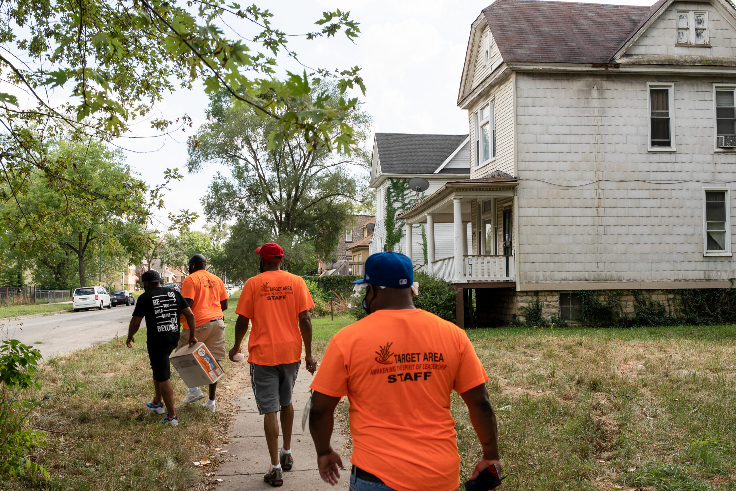 A team of outreach workers walks through a neighborhood in bright orange shirts.