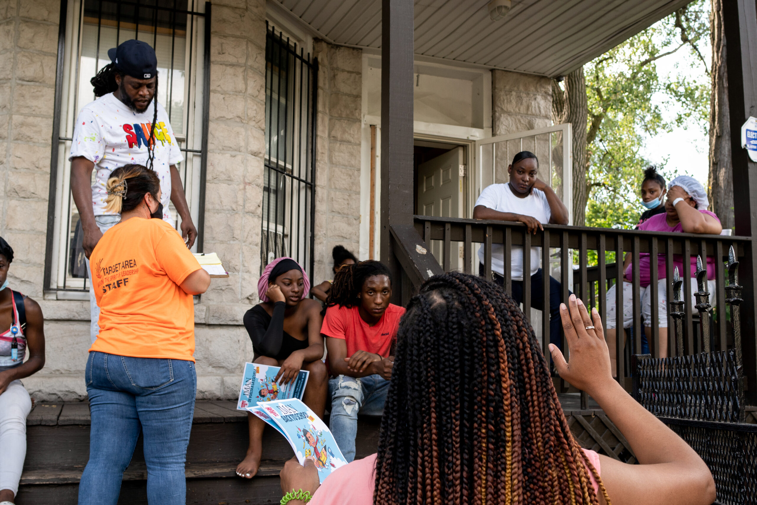Pastor Tracey gestures to a group of forlorn people standing on the front porch of their home.