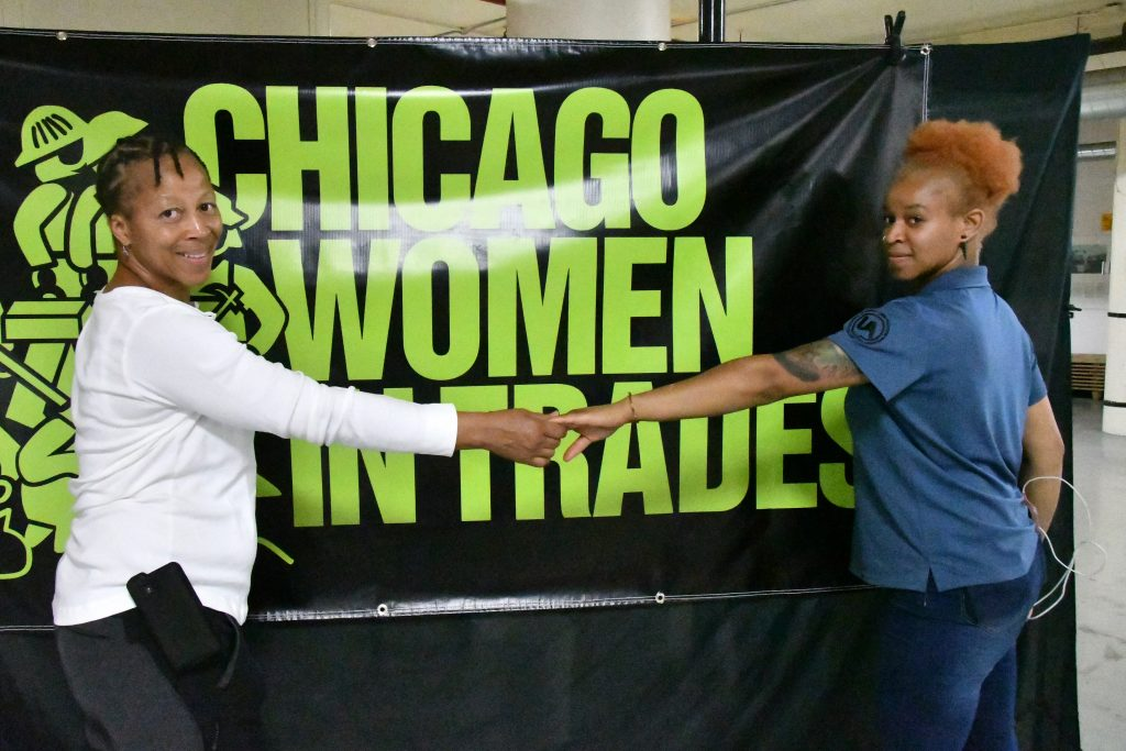 """Zahrah Hill and her mom, Renee, hold hands and smile in front of a sign that reads """"Chicago Women in Trades."""""""