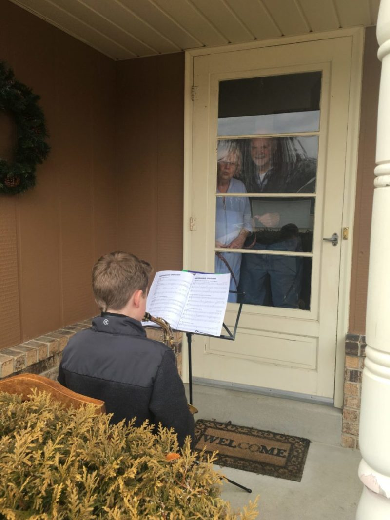 A little boy plays a saxophone while his grandparents listen and smile from their door.