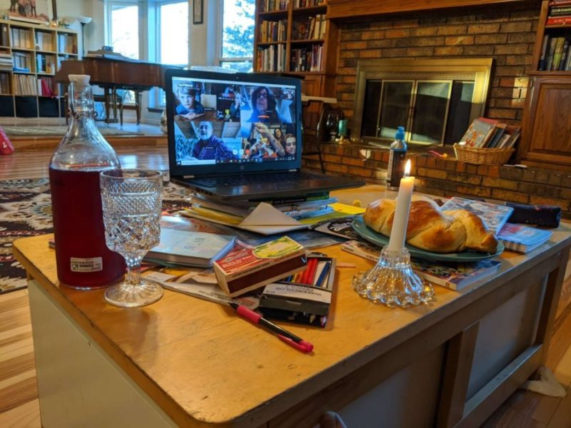 A laptop featuring Deborah's family is set up in front of their Shabbat meal.