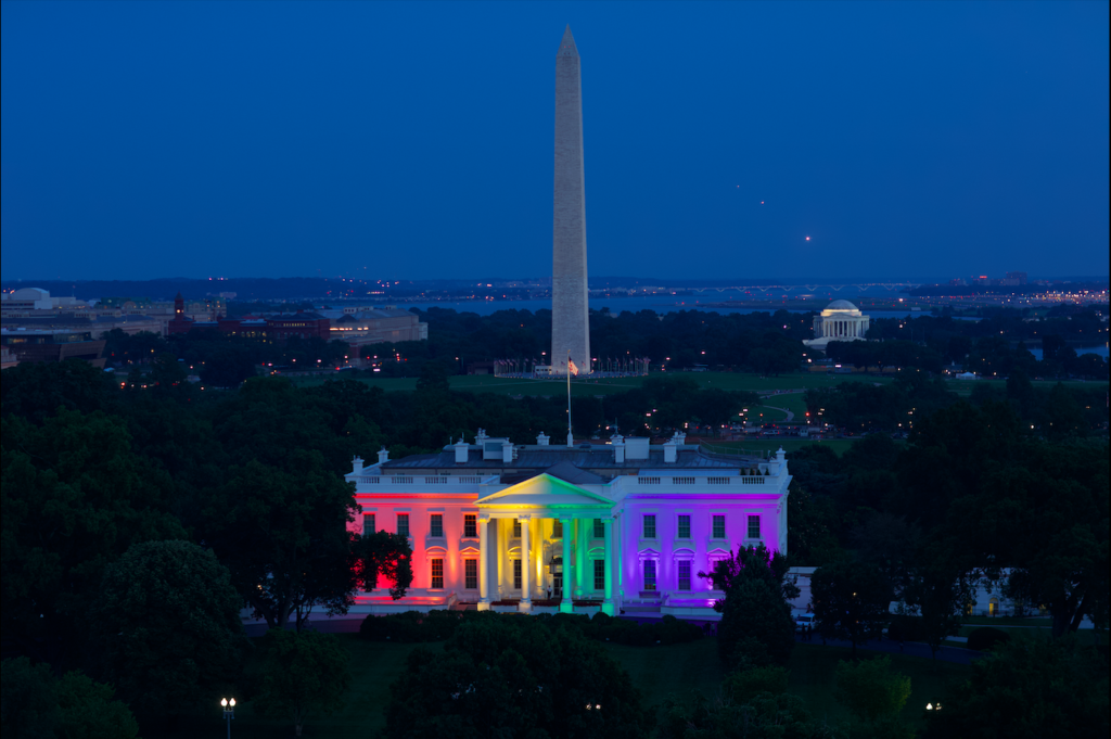 The White House lit in rainbow colors with the Washington Monument in view behind it.