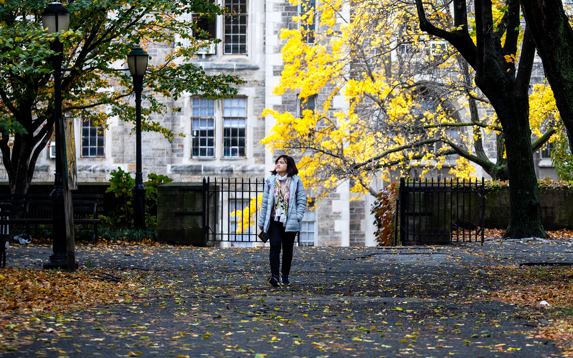 Hong Hoang walks in the park on a sunny, fall day.