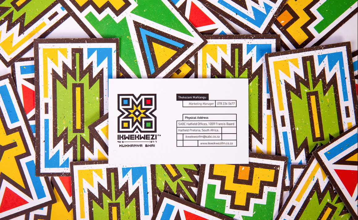 The business card of IKwekwzi FM is shown on a background of colorful geometric shapes.