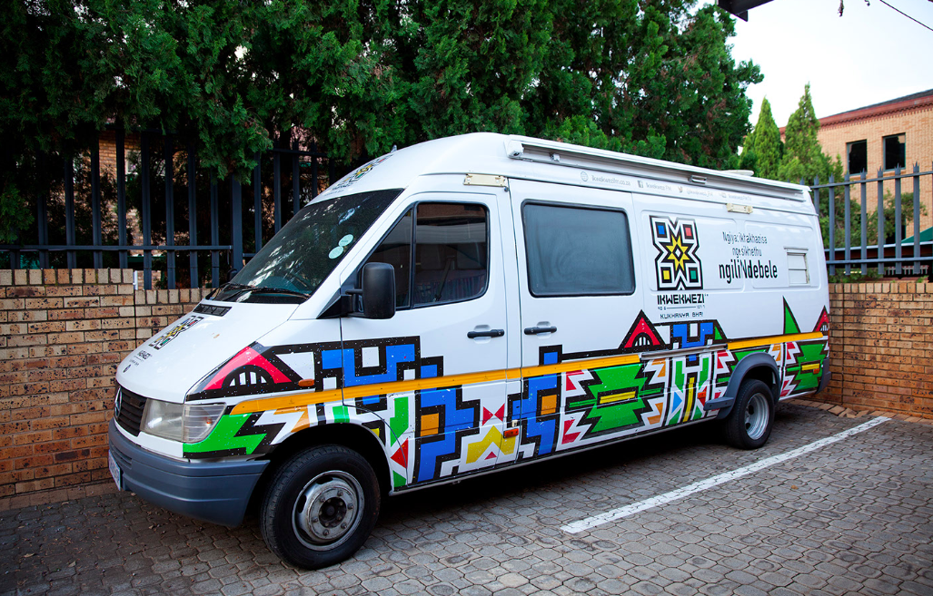 A white van is pictured with geometric shapes on it and the name IKwekwezi FM.