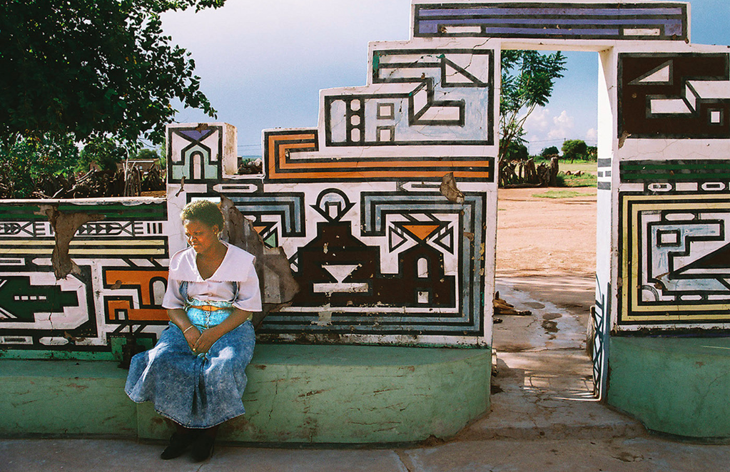 A woman sits in front of a wall structure with geometric shapes and designs.