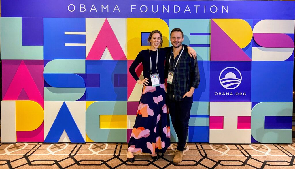 Skye and Tim smile in front of a colorful background at the Leaders: Asia-Pacific convening, 2019.