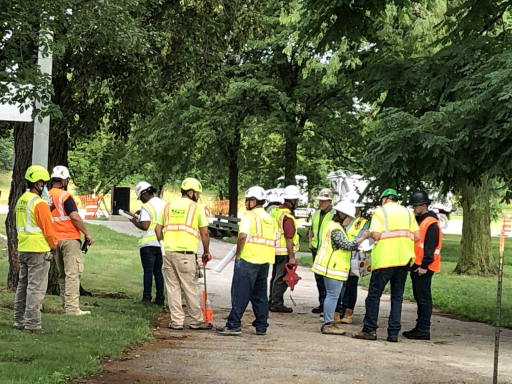 A group of construction workers wearing yellow shirts and white hardhats gather.