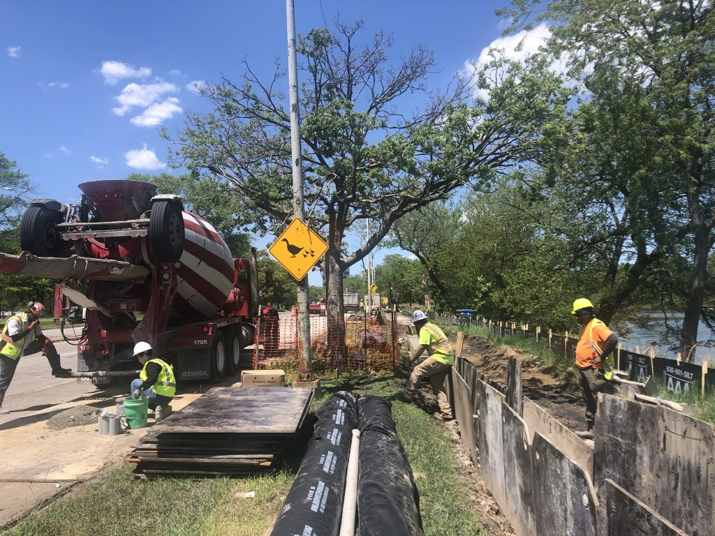 Utility lines are shown being placed into the ground.