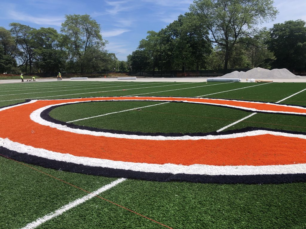 A football field with the Chicago Bears logo is shown at the 50-yard line.