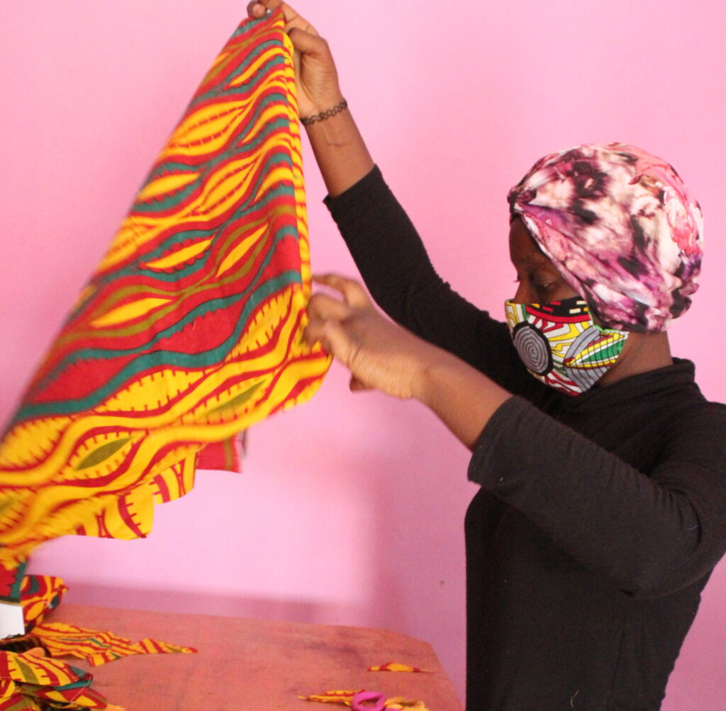 A woman holds up a patterned piece of cloth.