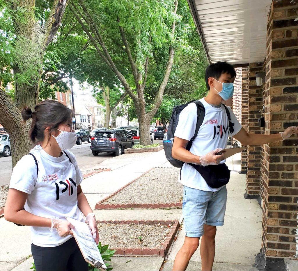 Two young people wearing masks knock on doors to speak with neighbors.