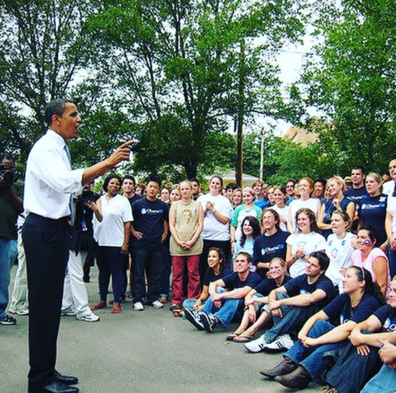 President Obama speaks to a group of young people outdoors.