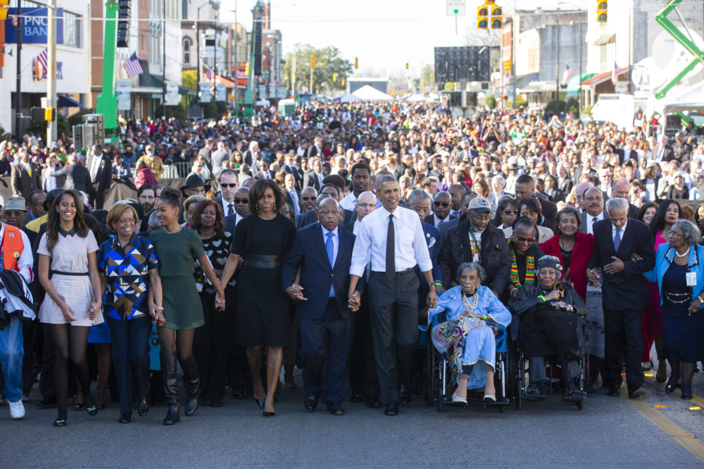 President Obama, his family, and thousands of people, and John Lewis cross the Edmund Pettus Bridge hand in hand.