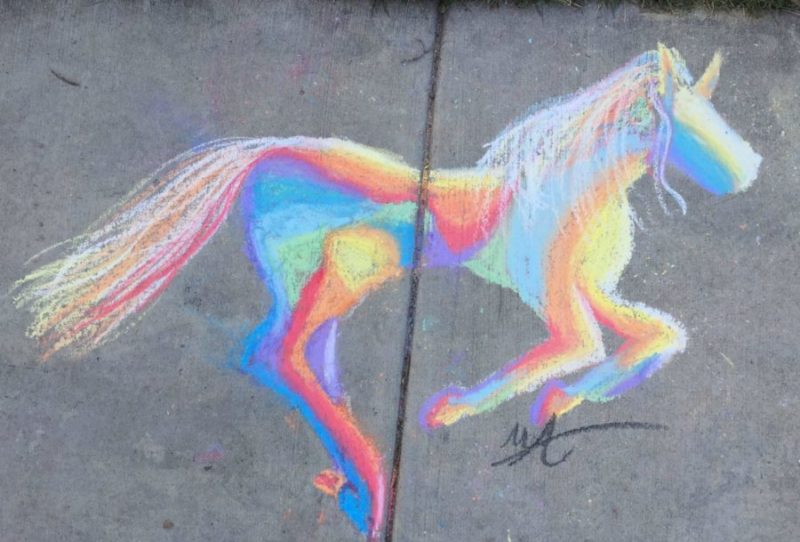 A chalk painting of a horse on a sidewalk.